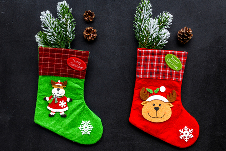 Christmas decoration. Traditional festive socks with spruce branch and pine cones on black background top view