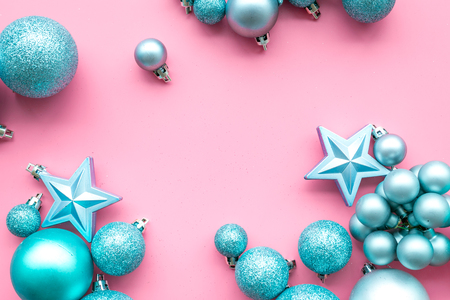 Christmas tree toys background. Blue balls and stars on pink background top view copy space border