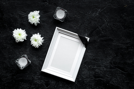 Death concept. Photo frame, mockup with black ribbon near flowers, candles on black background top view copy space