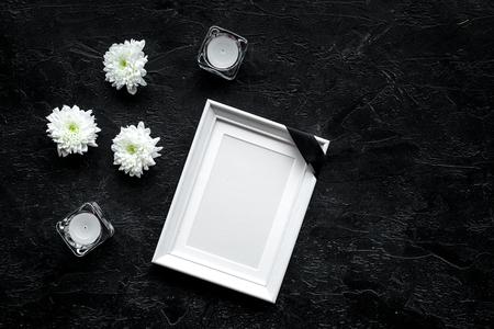 Tod Konzept. Fotorahmen, Modell mit schwarzem Band in der Nähe von Blumen, Kerzen auf schwarzem Hintergrund Draufsicht Kopie Raum