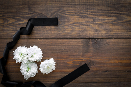 Funeral symbols. White flower near black ribbon on dark wooden background top view copy space Stock fotó