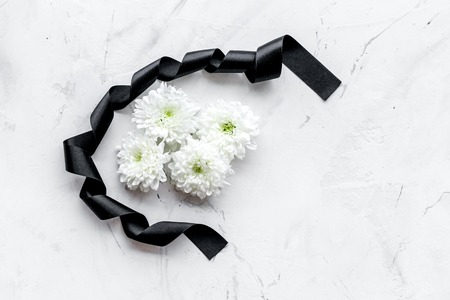 Funeral symbols. White flower near black ribbon on white stone background top view copy space