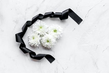 Funeral symbols. White flower near black ribbon on white stone background top view copy space Zdjęcie Seryjne - 112547703