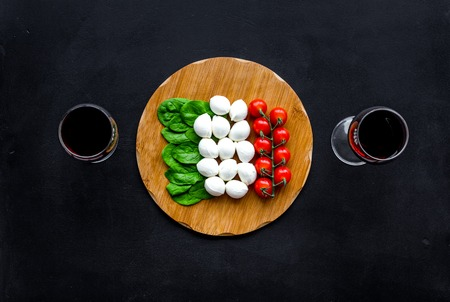 Italian cuisine, food concept. Italian flag made of mozzarella, tomatoes, basil on wooden cutting board near glass of red wine on black background top view copy space