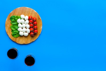 Italian cuisine, food concept. Italian flag made of mozzarella, tomatoes, basil on wooden cutting board near glass of red wine on blue background top view copy space Reklamní fotografie - 112547287