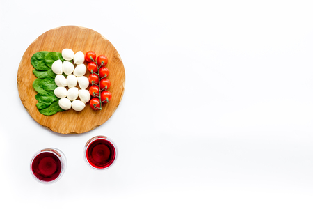 Italian cuisine, food concept. Italian flag made of mozzarella, tomatoes, basil on wooden cutting board near glass of red wine on white background top view space for text Reklamní fotografie - 112547291