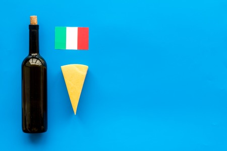 Gastronomical tourism. Italian food symbols. Italian flag, cheese parmesan and bottle of red wine on blue background top view space for text