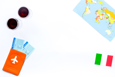 Gastronomical tourism. Italian food symbols. Passport and tickets near italian flag, glass of red wine, map of the world on white background top view copy space border Reklamní fotografie