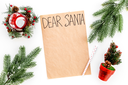 Letter to Santa Claus template. Mockup on craft paper with text Dear Santa near New Year decoration like fir branches, candle, festive tree on white background top view Stock Photo