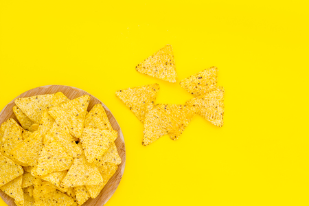 Mexican snack. Make nachos. Crispy nachos on wooden cutting board on yellow background top view copy space