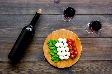 Italian cuisine, food concept. Italian flag made of mozzarella, tomatoes, basil on wooden cutting board near glass of red wine and wine bottle on dark wooden background top view Stockfoto