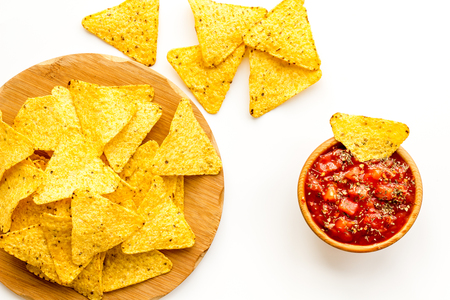 Snack for party. Mexican nachos near salsa sause on white background top view