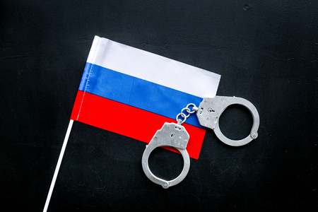 Violation of law, law-breaking concept. Metal handcuffs on russian flag on black background top view