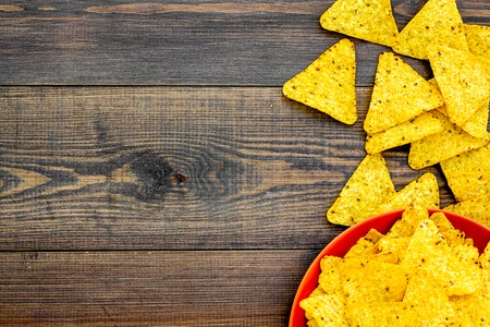 Mexican snack. Make nachos. Crispy nachos on plate on dark wooden background top view. Stock Photo