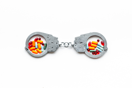 Arrest for illegal purchase, possession and sale drugs concept. Drugs as pills near handcuff on white background top view copy space Stock fotó