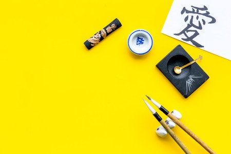 Chinese or japanese calligraphy concept. Hieroglyph love near traditional written accessories on yellow background top view copy space 版權商用圖片