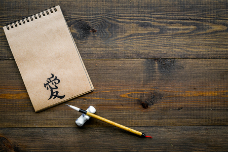 Chinese traditional calligraphy concept. Asian hieroglyph love in craft paper notebook near special writting pen on dark wooden background top view copy space