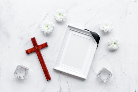 Funeral. Mockup of portrait of the deceased, of dead person. Frame with black ribbon near flowers, candles and cross on white background top view