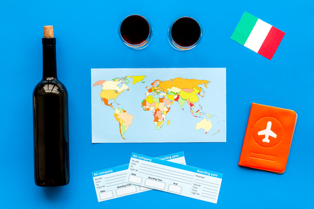 Gastronomical tourism. Italian food symbols. Passport and tickets near italian flag, bottle of red wine, map of the world, cheese parmesan on blue background top view Reklamní fotografie