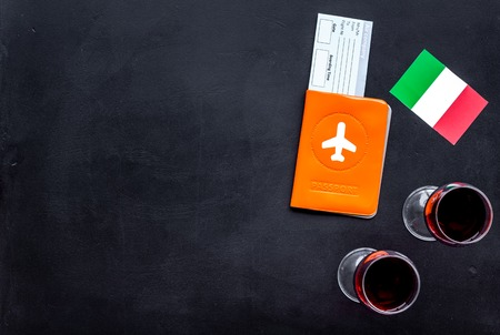 Gastronomical tourism. Italian food symbols. Passport and tickets near italian flag and glass of red wine on black background top view copy space