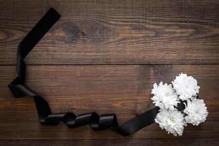 Begräbnissymbole. Weiße Blume in der Nähe von schwarzem Band auf dunklem Holzhintergrund Draufsicht Kopie Raum Standard-Bild