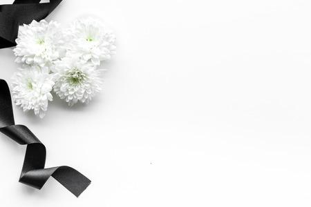 Begräbnissymbole. Weiße Blume in der Nähe von schwarzem Band auf weißem Hintergrund Draufsichtraum für Text