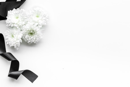 Funeral symbols. White flower near black ribbon on white background top view space for text