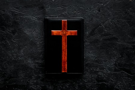 Farewell ceremony, funeral concept. Wooden cross on Bible on black background top view copy space