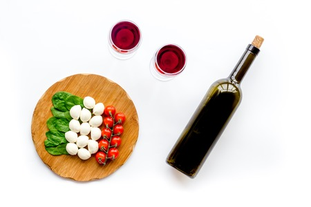 Italian cuisine, food concept. Italian flag made of mozzarella, tomatoes, basil on wooden cutting board near glass of red wine and wine bottle on white background top view Фото со стока
