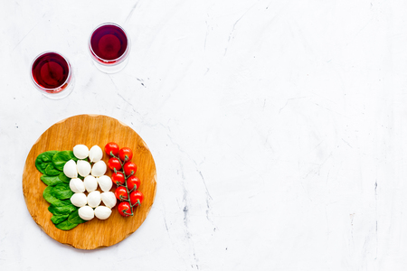 Italian cuisine, food concept. Italian flag made of mozzarella, tomatoes, basil on wooden cutting board near glass of red wine on white stone background top view copy space