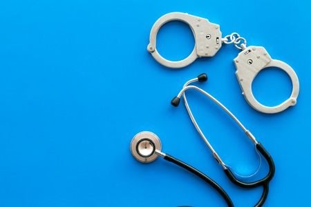 Medical lawsuit. Arrest for medical crime concept. Handcuff near stethoscope on blue background top view space for text