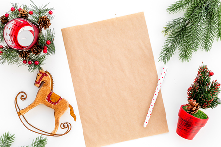 New Year or Christmas mockup. Template for letter to Santa, list of plans and goals for New Year, wishlist near fir branches, toy horse on white background top view Stock Photo