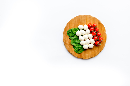 Italian flag made of mozzarella cheese, cherry tomatoes, green basil on wooden cutting board on white background top view space for text