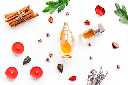 Perfume with bright fruity, floral, spicy fragrance. Ingredients for perfume. Bottle of perfume near dry flowers, cinnamon and candles on white background top view pattern