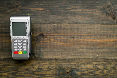 Payment terminal, compact POS terminal on dark wooden background top view copy space
