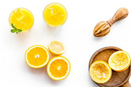 Squeeze fresh oranges with juicer. Orange juice in glass near half cut oranges on white background top view