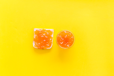 Sweet breakfast. Toast with peach jam on yellow background top view space for text Reklamní fotografie