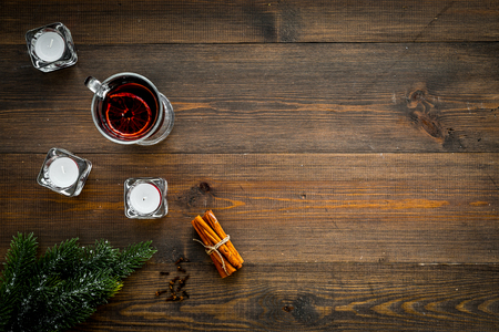Winter beverage for New Year or Christmas Eve. Mulled wine near fir branches, candles, cinnamon on dark wooden background top view copy space