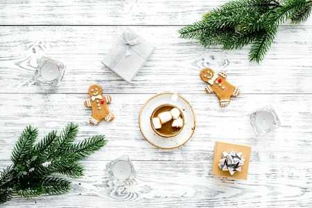 New Year or Christmas concept with hot drink. Cocoa with marshmallow, gift box fir branches on white wooden background top view.