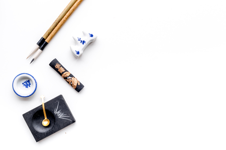 Accessories for chinese or japanese calligraphy. Special writting pen, ink on white background top view copy space