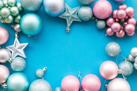 Christmas and New Year symbols. Toys for festive tree. Blue and pink balls and stars on blue background top view. Stock Photo