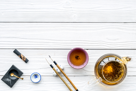 Chinese or japanese traditions. Calligraphy and tea ceremony concept. Special writting pen, ink near teapot and cup of tea on white wooden background top view.
