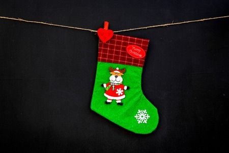Decorative christmas socks. Empty socks for gift hanging off a thread on black background top view.