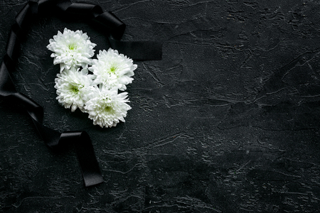 Funeral symbols. White flower near black ribbon on black background top view. Zdjęcie Seryjne