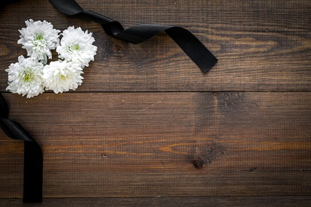 Funeral symbols. White flower near black ribbon on dark wooden background top view. Stock Photo