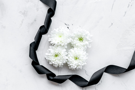 Funeral symbols. White flower near black ribbon on white stone background top view.