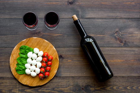 Italian cuisine, food concept. Italian flag made of mozzarella, tomatoes, basil on wooden cutting board near glass of red wine and wine bottle on dark wooden background top view.