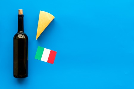 Gastronomical tourism. Italian food symbols. Italian flag, cheese parmesan and bottle of red wine on blue background top view.