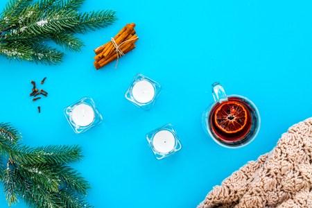 Hot beverage for warm winter evening. Mulled wine near cinnamon, fir branches, wool blanket, candles on blue background top view.