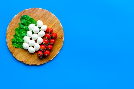 Italian flag made of mozzarella cheese, cherry tomatoes, green basil on wooden cutting board on blue background top view space for text